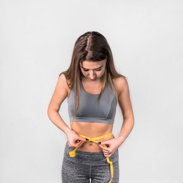 Attraente donna sottile che misura la vita Foto Gratuite