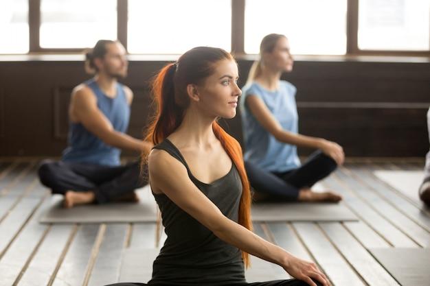 Attraente donna yogi e un gruppo di persone a matsyendrasana Foto Gratuite