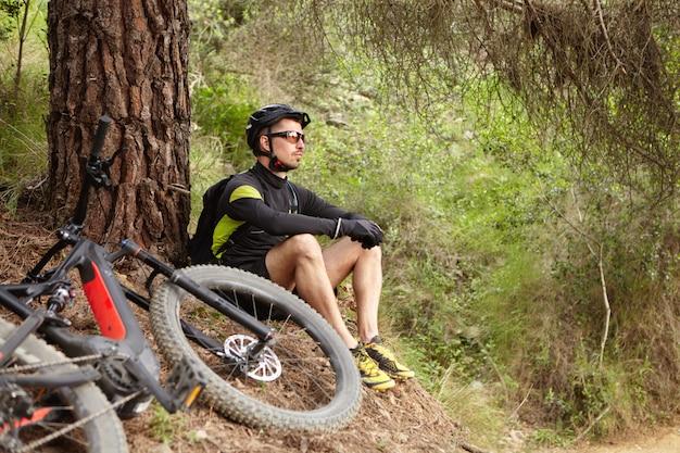 Attraente giovane cavaliere europeo in equipaggiamento protettivo seduto a terra sull'albero, contemplando la straordinaria natura selvaggia che lo circonda mentre si riposa dopo un intenso allenamento in bicicletta nella foresta sulla sua e-bike Foto Gratuite