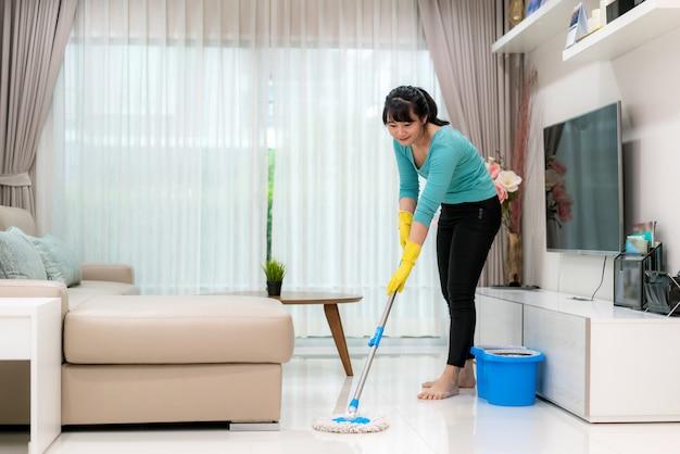 Attraente giovane donna asiatica rastrellamento di piastrelle a pavimento durante il soggiorno mentre si fa la pulizia a casa durante il soggiorno a casa usando il tempo libero sulla loro routine di pulizia quotidiana. Foto Premium