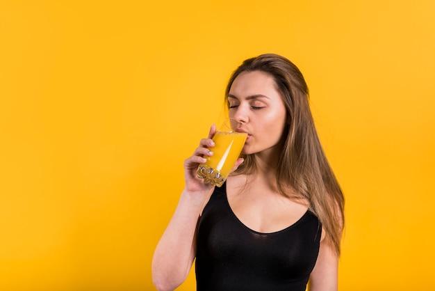 Attraente giovane donna che beve succo di vetro Foto Gratuite