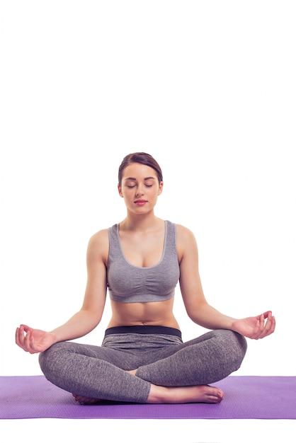 Attraente giovane donna in abbigliamento sportivo sta meditando. Foto Premium