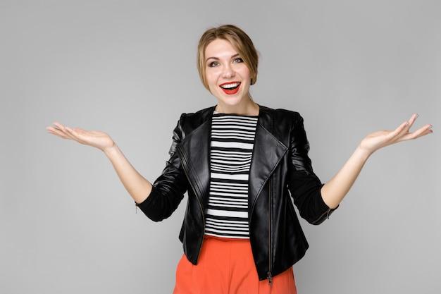 Attraente giovane ragazza bionda in camicia a righe e giacca di pelle sorridente che ride con le mani aperte in piedi Foto Premium