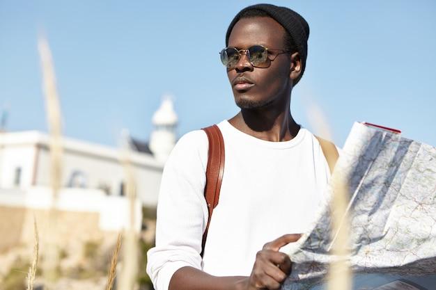 Attraente giovane turista maschio nero in occhiali da sole alla moda e cappello tenendo la carta cartacea e guardando in giro con espressione seria e concentrata, cercando di trovare il modo di hotel dopo essersi perso Foto Gratuite