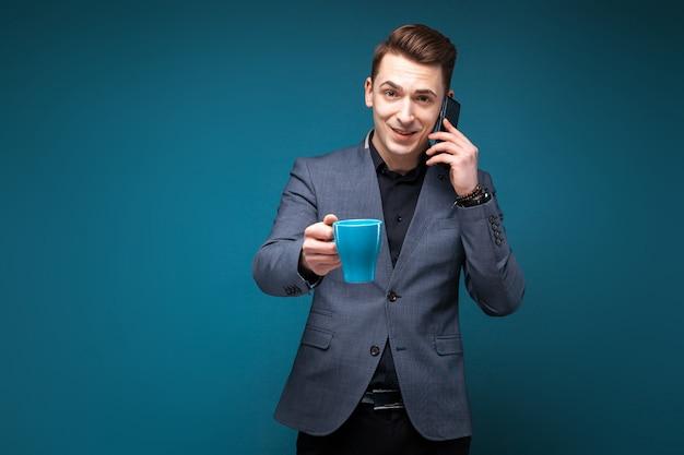 Attraente giovane uomo d'affari in giacca grigia e camicia nera tenere tazza blu e parlare al telefono Foto Premium