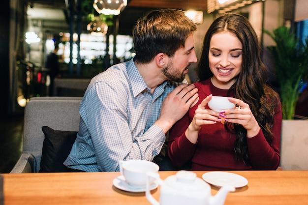 Attraente ragazza è seduta sul divano del ristorante e beve un po 'di tè mentre la sua compagna le mette una mano sulla spalla e la guarda. lei sta sorridendo. Foto Premium