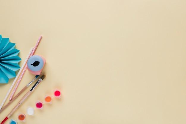 Attrezzatura artigianale e ventilatore di carta origami blu su sfondo beige Foto Gratuite
