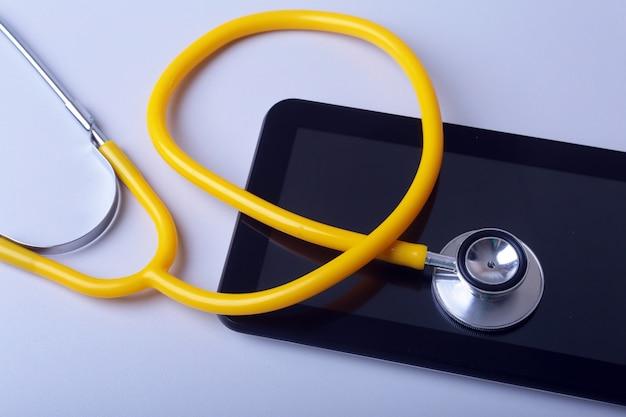 Attrezzatura medica: stetoscopio e compressa blu su fondo bianco Foto Premium