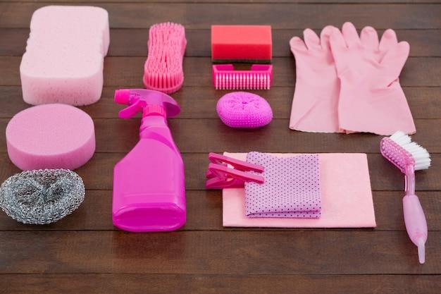 Attrezzature per la pulizia di colore rosa sistemate sul pavimento di legno Foto Premium