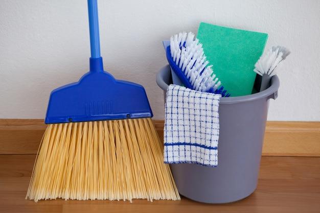 Attrezzature per la pulizia sul pavimento di legno contro la parete Foto Premium