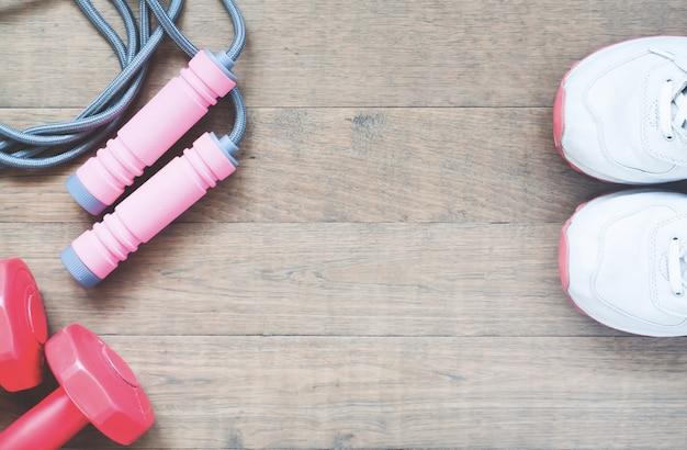 Attrezzature sportive con scarpe sportive su sfondo di legno, stile di vita sano e concetto di lavoro Foto Premium