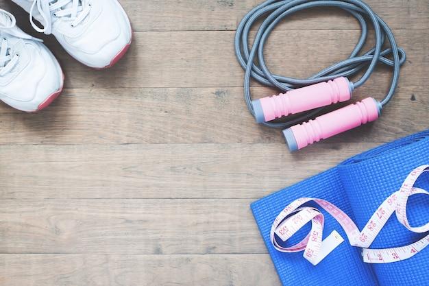 Attrezzature sportive e yoga con nastro di misura su fondo in legno con spazio di copia Foto Premium
