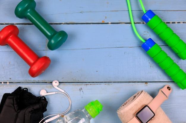 Attrezzature sportive per allenamento fitness su uno sfondo di legno. Foto Premium