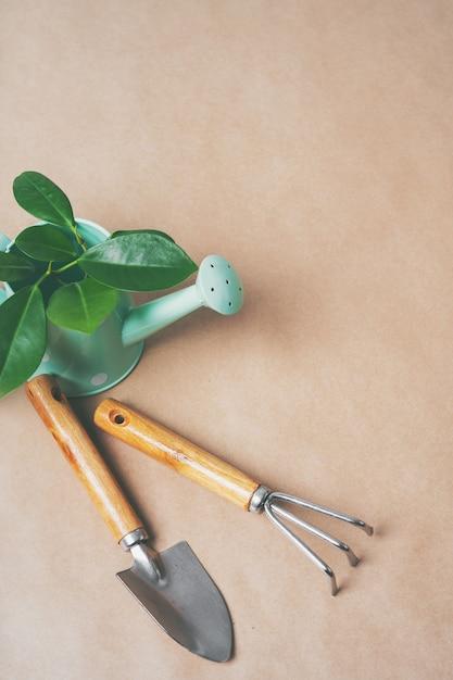 Attrezzi da giardinaggio, vasi di carta, annaffiatoio su carta artigianale con copia spazio. dalla pentola al giardino. Foto Premium