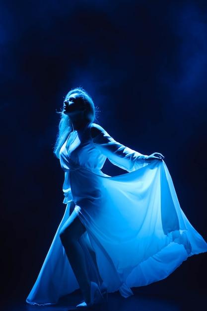 Attrice / cantante sul palco nei raggi di luce blu. Foto Premium