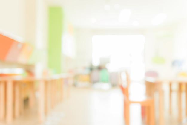 Aula scolara in sfocatura sfondo senza giovane studente; vista sfocata della sala di classe elementare nessun ragazzo o insegnante con sedie e tavoli nel campus. immagini di stile d'effetto vintage. Foto Gratuite
