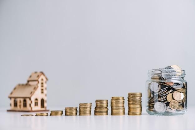 Aumentando le monete impilate e il barattolo di vetro davanti al modello di casa Foto Gratuite