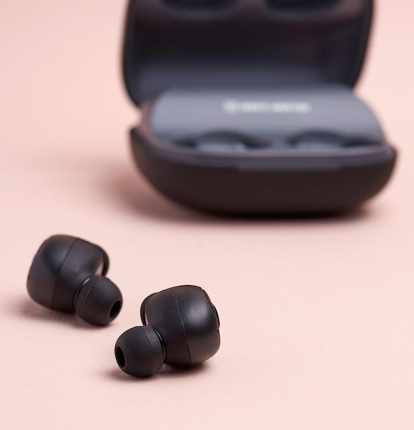 Auricolari wireless neri e una scatola di ricarica Foto Premium