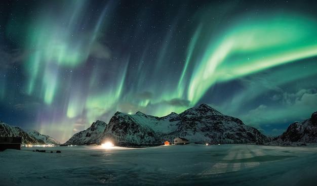 Aurora boreale o aurora boreale sopra la montagna di neve sulla costa Foto Premium
