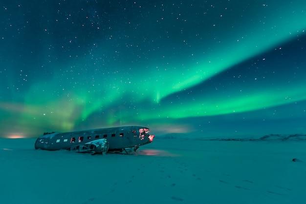 Aurora boreale sopra il relitto piano in islanda Foto Premium