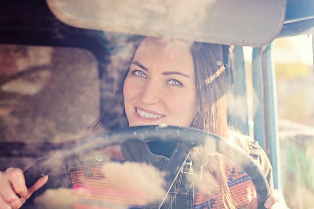 Autista di camion della donna in macchina. ragazza che sorride alla macchina fotografica e che tiene il volante. Foto Premium