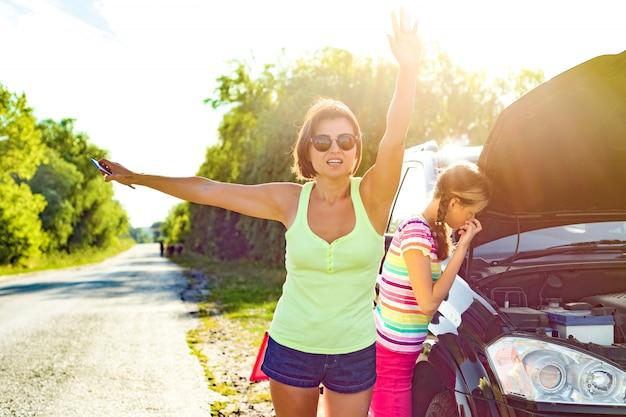 Autista donna con bambino vicino auto rotta. Foto Premium