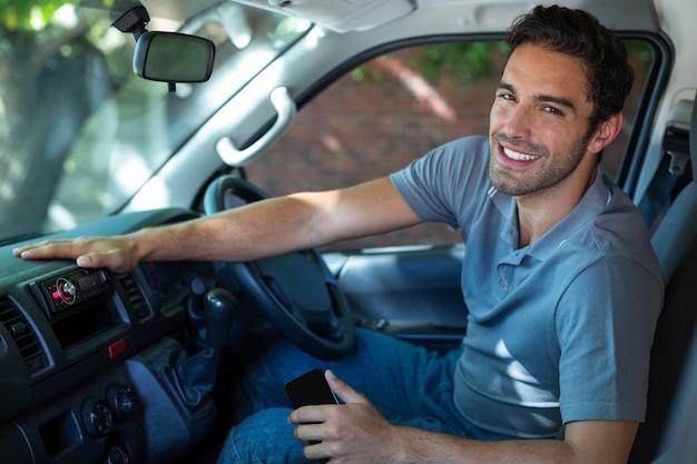 Autista sorridente seduto in macchina Foto Premium