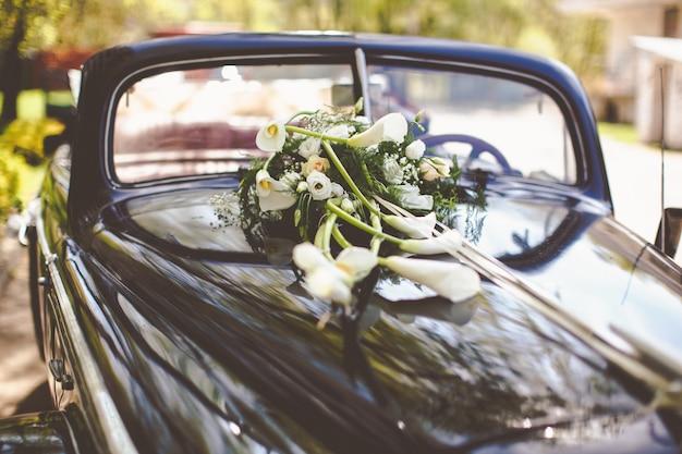 Auto d'epoca nera decorata con calle per un viaggio di nozze Foto Gratuite