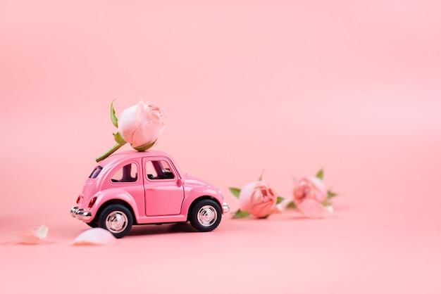 Auto giocattolo rosa retrò offre un fiore rosa su sfondo rosa. Foto Premium