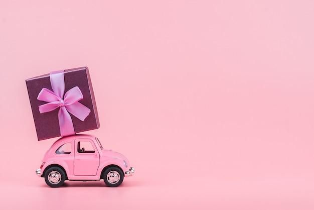 Auto giocattolo rosa retrò offre un regalo su sfondo rosa. cartolina del 14 febbraio, san valentino. consegna fiori giorno delle donne Foto Premium