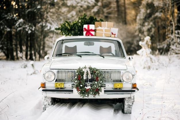 Auto retrò con regali e albero di natale nella foresta di inverno nevoso e bella corona di natale. Foto Premium