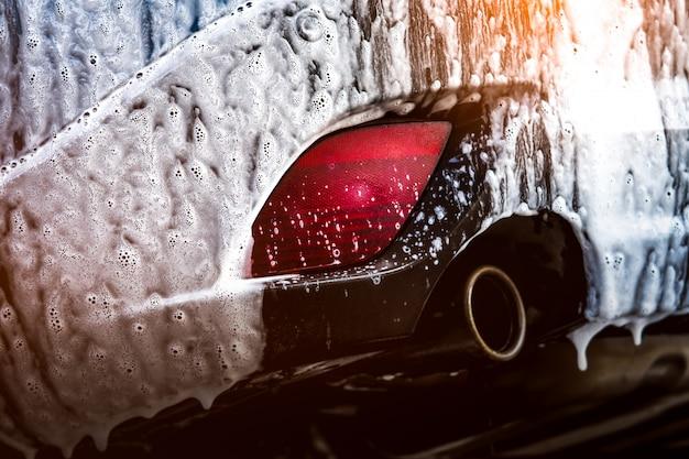 Auto suv compatta blu con sport e design moderno che lava con sapone. auto coperta di schiuma bianca. concetto di affari di servizio di cura dell'automobile. autolavaggio con schiuma prima della ceratura del vetro e rivestimento in vetro dell'automobile Foto Premium