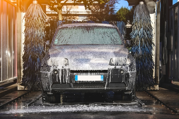 Autolavaggio schiuma acqua autolavaggio automatico in azione Foto Premium