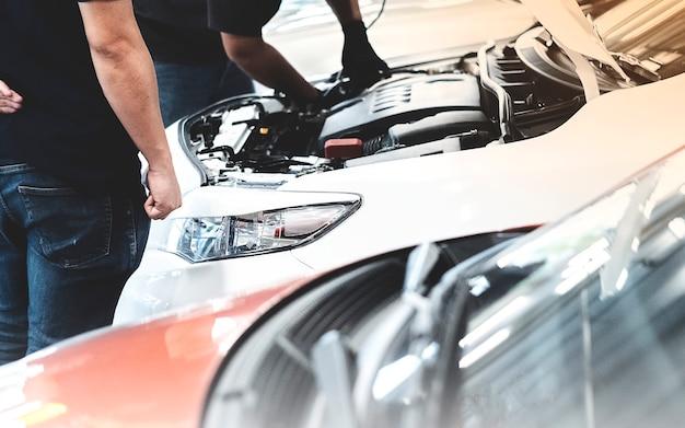 Automobile del cliente di riparazione del meccanico automatico al garage Foto Premium