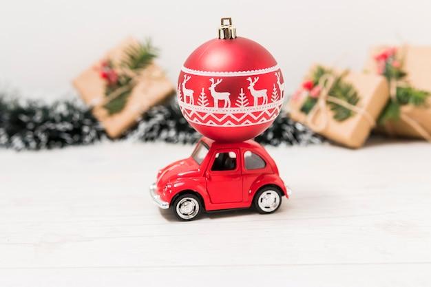Automobile del giocattolo con la palla rossa di natale vicino alle scatole attuali Foto Gratuite