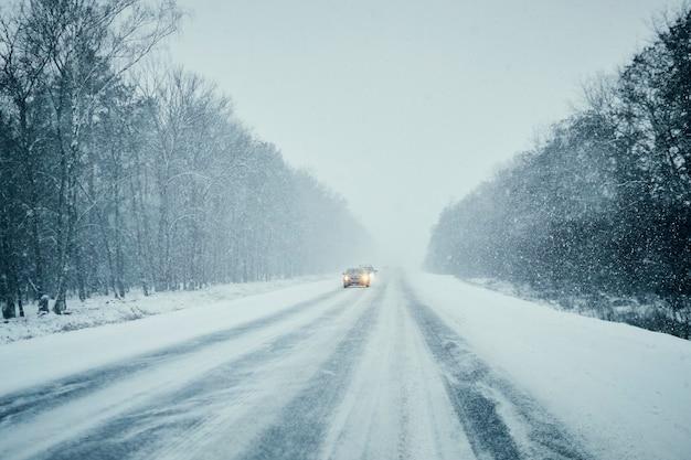 Automobile in tempesta sulla strada di inverno con traffico. pericolo di guida in inverno. visuale in prima persona Foto Premium