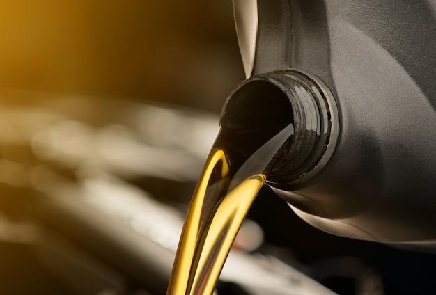 Automobile lubrificante di versamento dell'olio lubrificante dalla bottiglia nera su priorità bassa bianca isolata Foto Premium