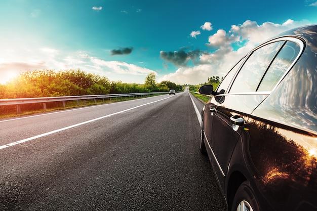 Automobile nera sulla strada asfaltata Foto Premium