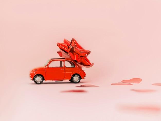 Automobile rossa del retro giocattolo rosso con l'arco rosso per il san valentino su fondo rosa con i coriandoli del cuore. 14 febbraio. 8 marzo, giornata internazionale della donna. messa a fuoco selettiva Foto Premium