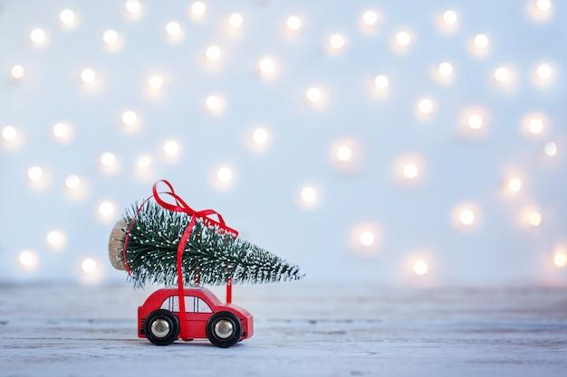 Automobile rossa miniatura con l'albero di abete di natale su fondo di legno. concetto di vacanza Foto Premium