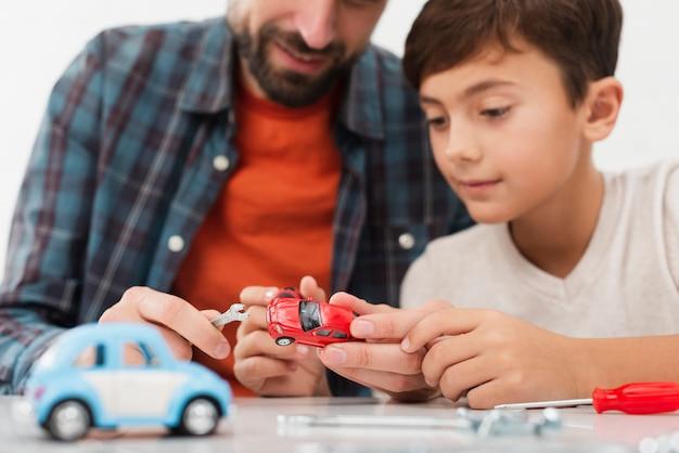 Automobili artistiche del giocattolo della riparazione del figlio della foto con il padre Foto Gratuite