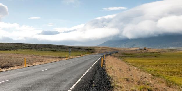 Autostrada asfaltata che scompare verso l'orizzonte verso le montagne coperte di zolle Foto Premium
