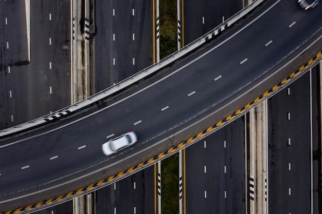 Autostrada e tangenziale dell'autostrada senza pedaggio del trasporto dell'automobile di traffico di vista aerea alla sera Foto Premium