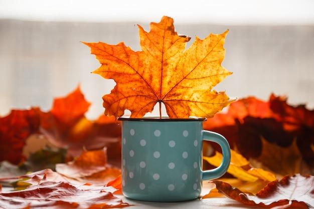 Autunno. foglie cadute e una tazza rustica di tè caldo Foto Premium