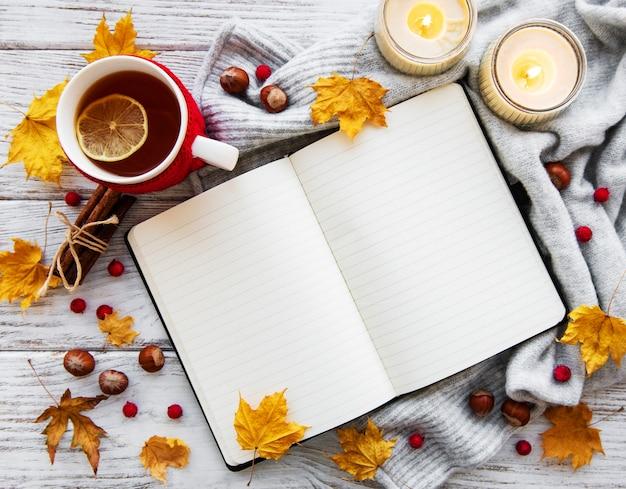 Autunno piatto giaceva con notebook, tazza di tè e foglie Foto Premium