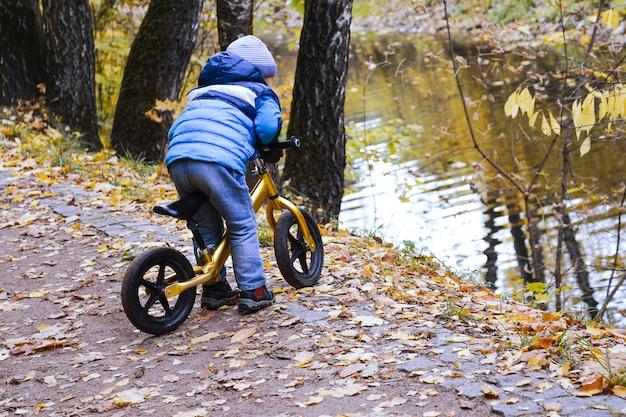 Autunno. un ragazzino guida una bici lungo un sentiero nel parco vicino al fiume. lui cavalca sul bordo della scogliera. Foto Premium