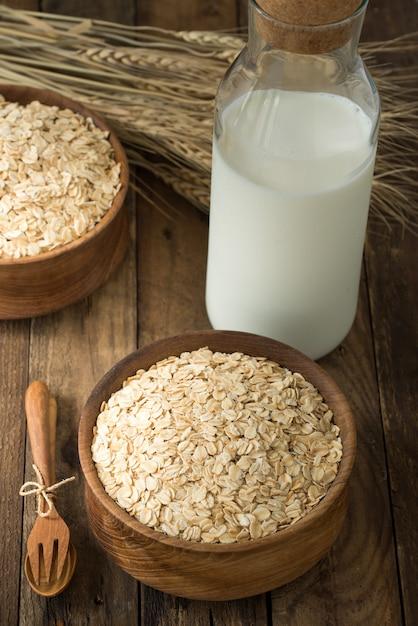 Avena rotolata, avena in scodella e brocca di latte su legno Foto Premium