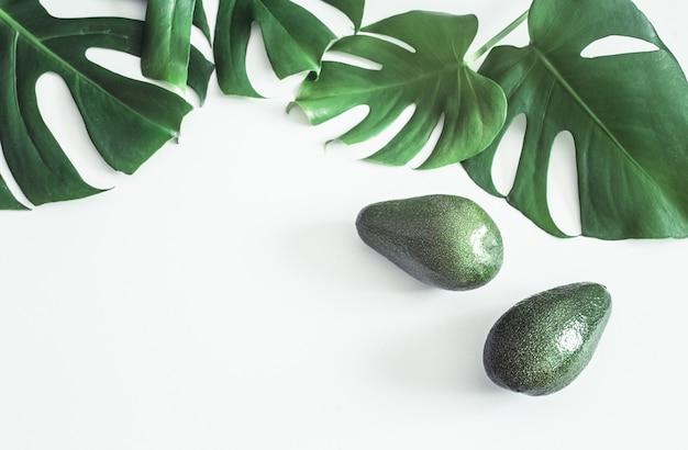 Avocado con foglie tropicali su sfondo bianco Foto Gratuite