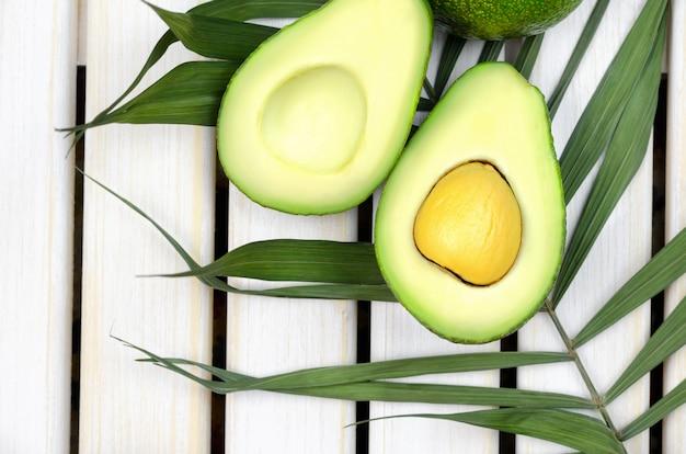 Avocado su fondo di legno bianco. Foto Premium