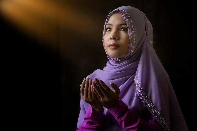 Avvicinamento. donne musulmane che indossano camicie viola. preghiera secondo i principi dell'islam. Foto Premium